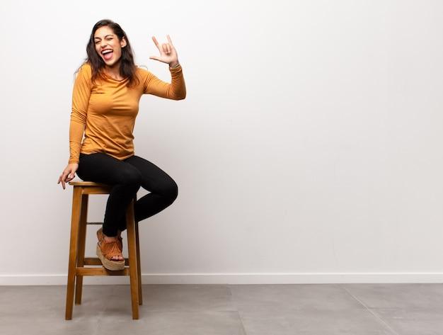 Jeune jolie femme criant agressivement avec une expression de colère ou avec les poings serrés célébrant le succès assis dans une pièce