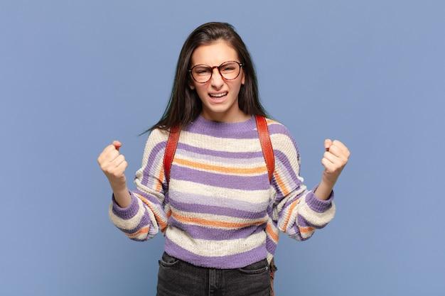 Jeune jolie femme criant agressivement avec un regard agacé, frustré, en colère et des poings serrés, se sentant furieuse. concept d'étudiant