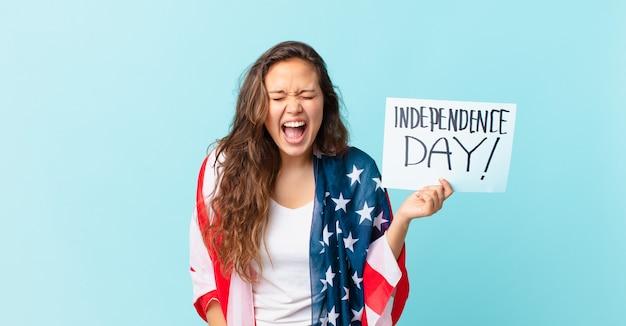 Jeune jolie femme criant agressivement, regardant le concept de la fête de l'indépendance très en colère