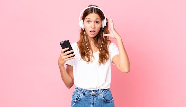 Jeune jolie femme criant avec les mains en l'air avec des écouteurs et un smartphone