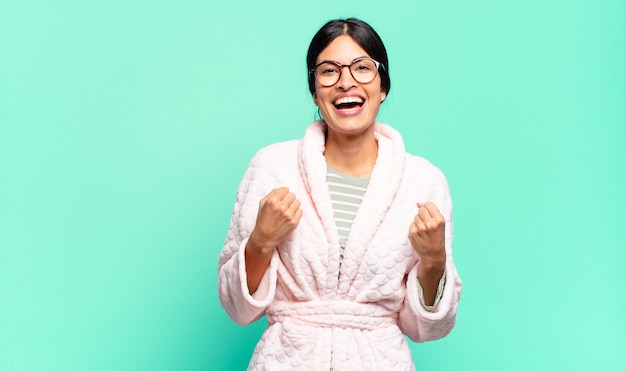 Jeune jolie femme criant triomphalement, riant et se sentant heureuse et excitée tout en célébrant le succès