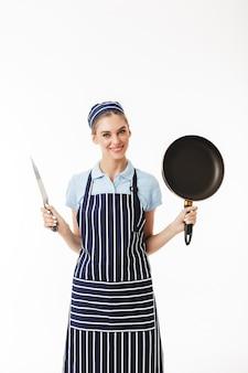 Jeune jolie femme cuisinier en tablier rayé et casquette heureusement