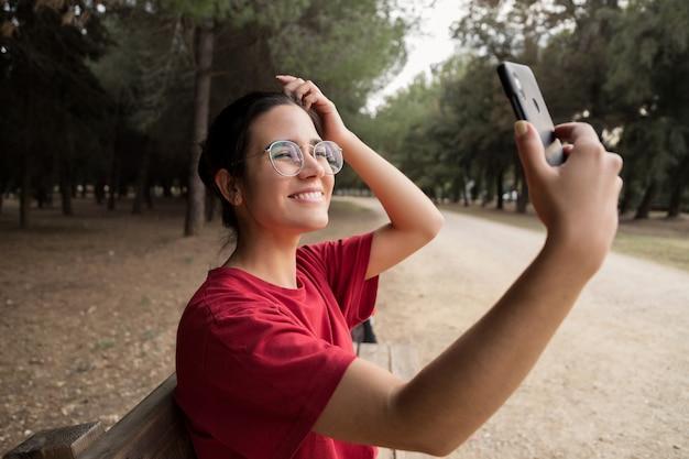 Jeune jolie femme dans la vingtaine avec des lunettes et une chemise rouge assise sur un banc, tenant un téléphone mobile et prenant un selfie tout en souriant dans un magnifique parc. elle regarde le téléphone