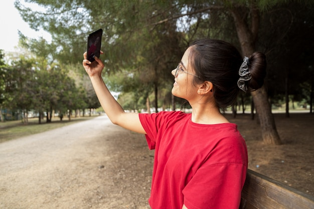 Jeune jolie femme dans la vingtaine avec des lunettes et une chemise rouge assise sur un banc, tenant un téléphone portable et prenant un selfie tout en souriant dans un magnifique parc en espagne. elle regarde le téléphone