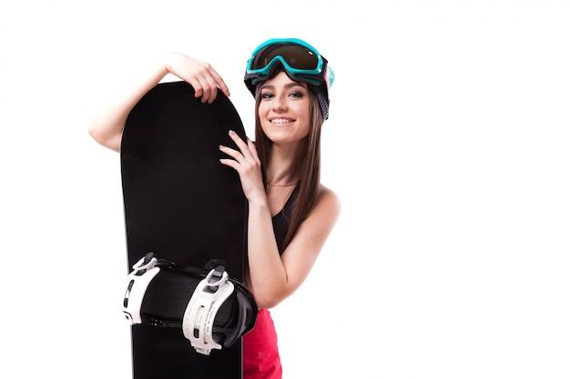 Jeune jolie femme en débardeur court noir tenir snowboard