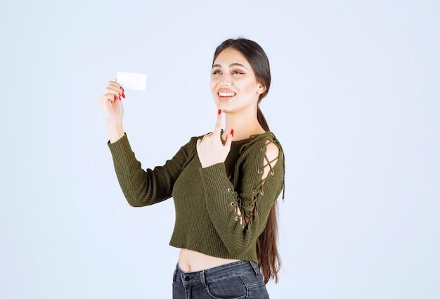 Jeune jolie femme debout avec une carte de visite vierge sur fond blanc.