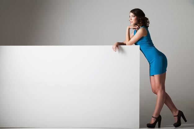 Jeune, jolie femme debout près d'un énorme tableau blanc et le tenant. beaucoup de copyspace pour votre texte et logo