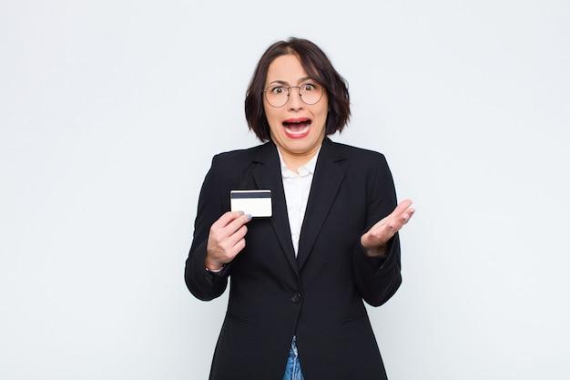 Jeune jolie femme désespérée et frustrée, stressée, malheureuse et ennuyée, criant et criant avec une carte de crédit