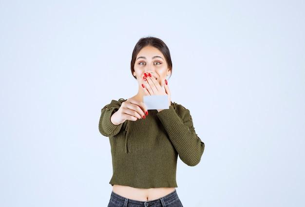 Jeune jolie femme donnant une carte de visite vierge et couvrant sa bouche.