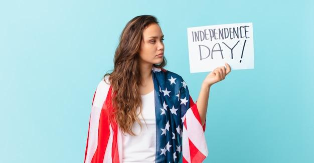 Jeune jolie femme avec drapeau américain et placard avec le texte : jour de l'indépendance