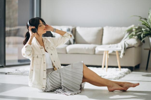 Jeune jolie femme écoutant de la musique sur des écouteurs sans fil
