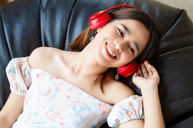 Jeune jolie femme écoute une chanson avec un casque