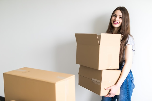 Jeune jolie femme emménageant dans un nouvel appartement tenant des boîtes en carton avec des effets personnels