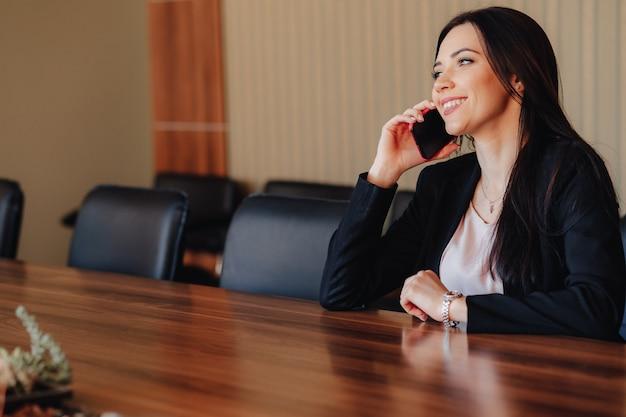 Jeune jolie femme émotionnelle dans des vêtements de style affaires assis au bureau avec téléphone