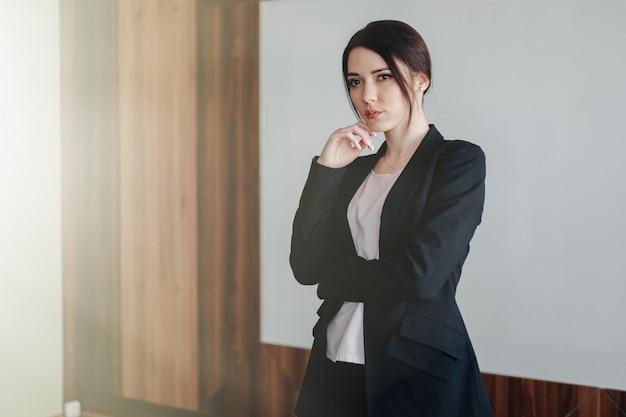 Jeune jolie femme émotionnelle dans des vêtements de style affaires