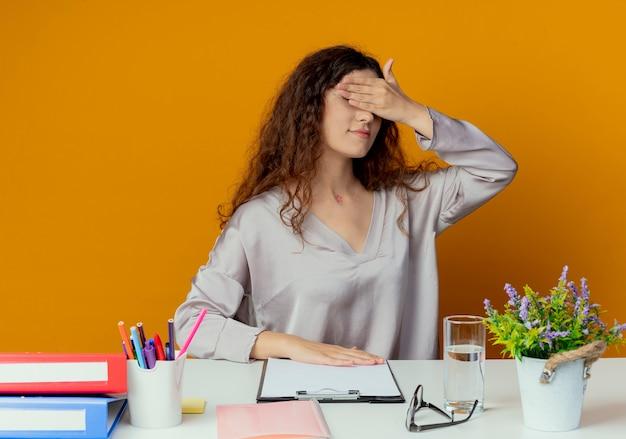 Jeune jolie femme employé de bureau assis au bureau avec des outils de bureau couverts yeux avec main isolé sur orange