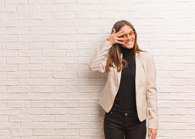 Jeune jolie femme entrepreneur gênée et riant en même temps