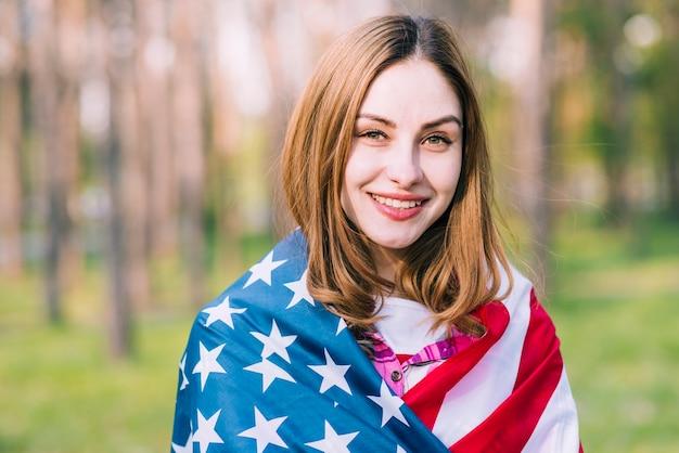 Jeune jolie femme envelopper dans le drapeau des etats-unis à l'extérieur