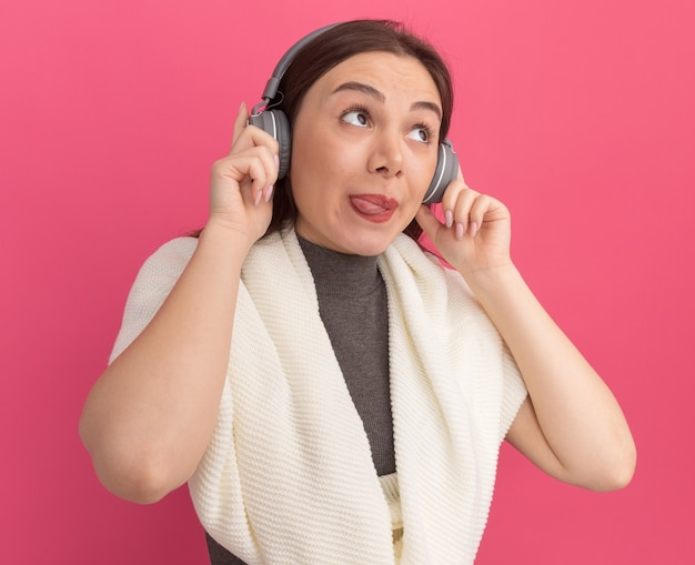 Jeune jolie femme espiègle portant et saisissant des écouteurs montrant la langue regardant le côté isolé sur le mur rose