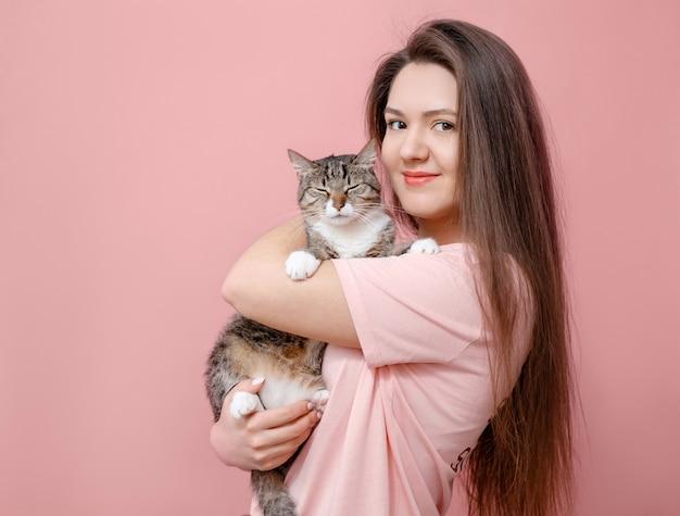 Jeune jolie femme étreignant le chat dans les mains, fond rose