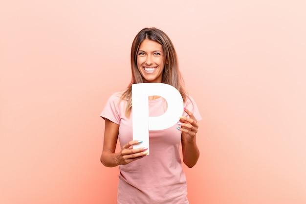 Jeune jolie femme excitée, heureuse, joyeuse, tenant la lettre p de l'alphabet pour former un mot ou une phrase.