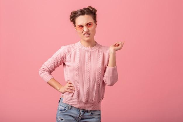 Jeune jolie femme avec l'expression du visage drôle, poiting doigt, se sentir dégoûté, en pull rose et lunettes de soleil isolé sur fond rose studio