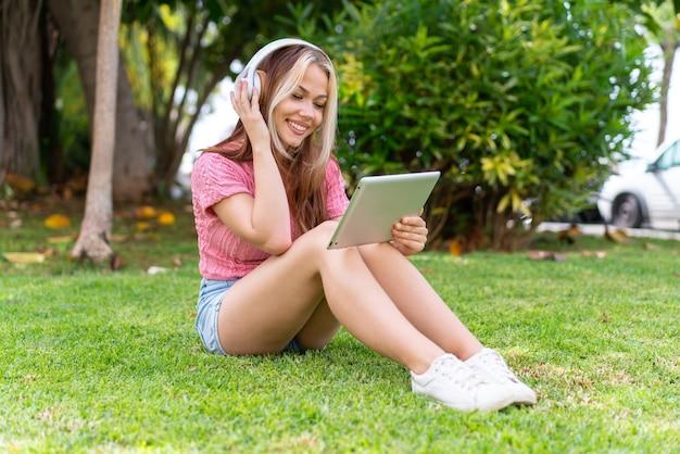 Jeune jolie femme à l'extérieur écoutant de la musique avec le mobile et heureuse