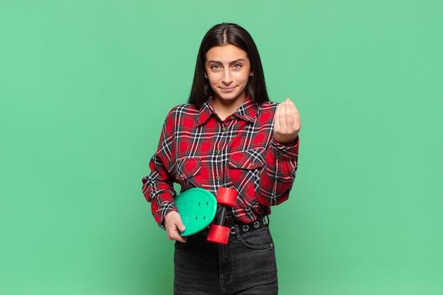 Jeune jolie femme faisant capice ou geste d'argent, vous disant de payer vos dettes!. concept de planche à roulettes