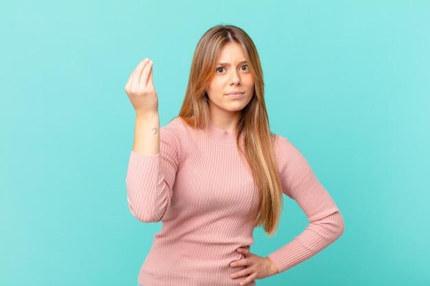 Jeune jolie femme faisant un geste de capice ou d'argent, vous disant de payer