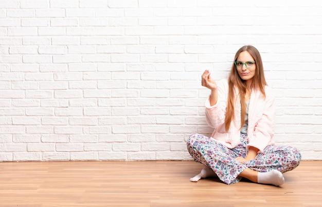 Jeune jolie femme faisant des gestes de capice ou d'argent, vous disant de payer vos dettes! . concept de maison