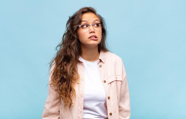 Jeune jolie femme sur fond bleu avec des lunettes