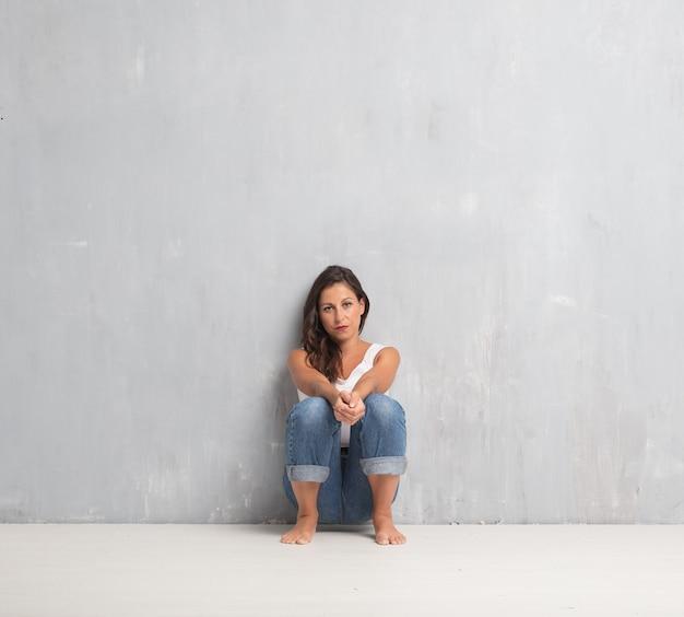 Jeune jolie femme sur fond de mur de ciment avec une copie sp