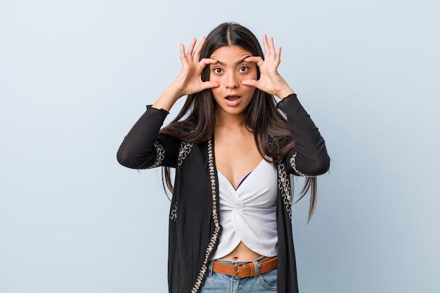 Jeune jolie femme gardant les yeux ouverts pour trouver une opportunité de réussite