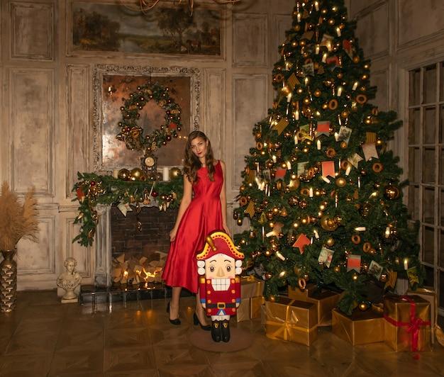 Jeune jolie femme en gros plan de robe rouge avec des décorations de noël