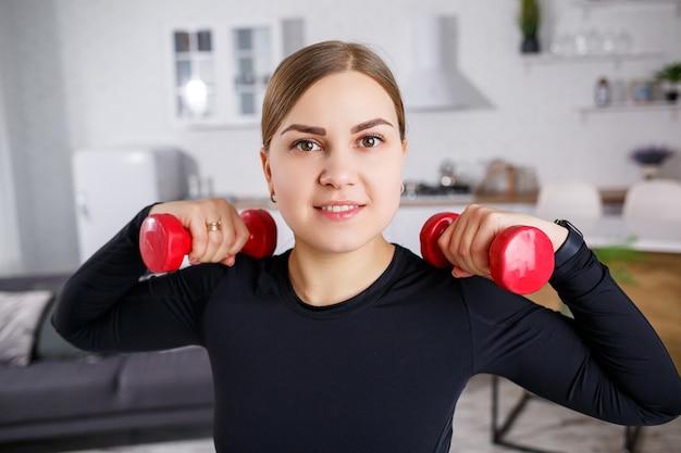 Jeune jolie femme en haut noir avec des haltères dans les mains faisant du sport à la maison, fitness à la maison pendant la quarantaine. mode de vie sain