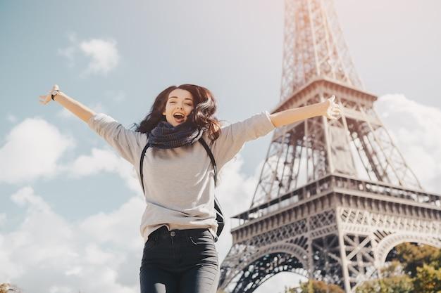 Jeune jolie femme heureuse sautant de joie contre la tour eiffel à paris, france. portrait de