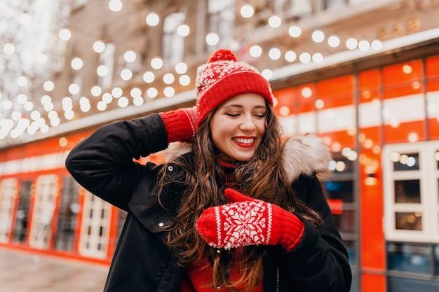 Jeune jolie femme heureuse souriante dans des mitaines rouges et bonnet tricoté portant un manteau d'hiver marchant dans la rue de la ville, des vêtements chauds