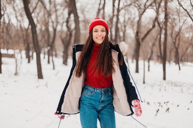 Jeune jolie femme heureuse souriante en mitaines rouges et bonnet tricoté portant un manteau d'hiver, marchant dans le parc dans la neige, des vêtements chauds