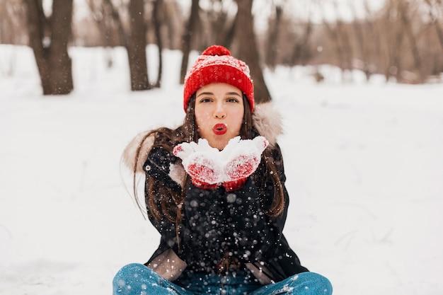 Jeune jolie femme heureuse souriante en mitaines rouges et bonnet tricoté portant un manteau d'hiver, marchant dans le parc, jouant avec la neige dans des vêtements chauds