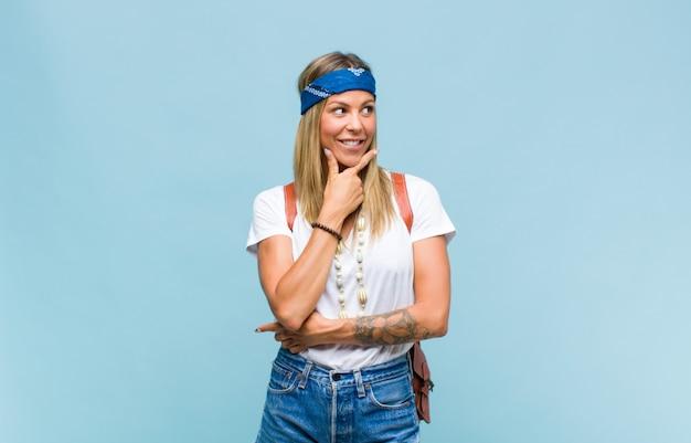 Jeune jolie femme hippie souriante avec une expression heureuse et confiante avec la main sur le menton, se demandant et regardant sur le côté