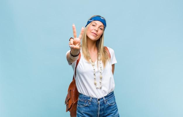 Jeune jolie femme hippie souriante et à la recherche heureuse, insouciante et positive, gestes de victoire ou de paix d'une main