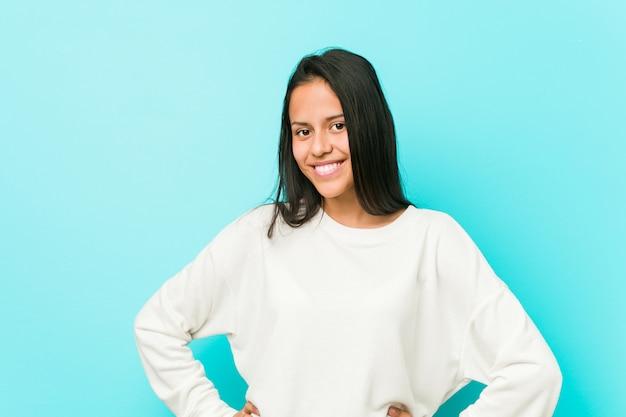 Jeune jolie femme hispanique confiante en gardant les mains sur les hanches.