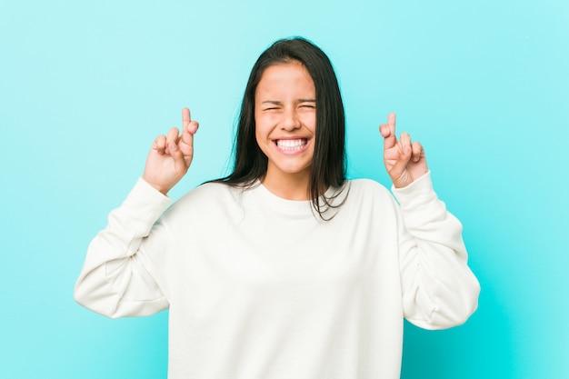 Jeune jolie femme hispanique croise les doigts pour avoir de la chance