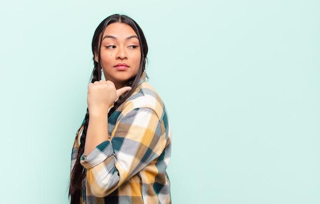 Jeune jolie femme hispanique avec un espace de copie contre un mur isolé