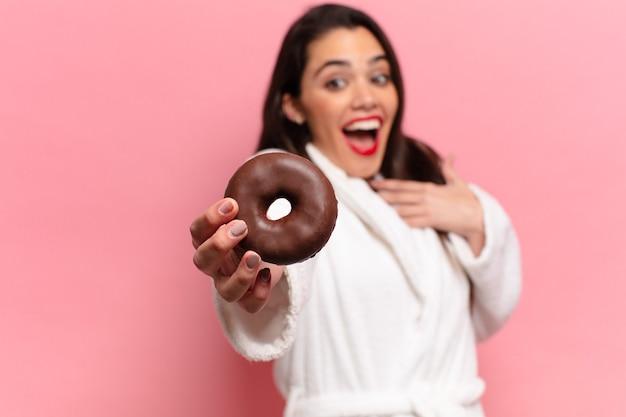 Jeune jolie femme hispanique expression heureuse et surprise tenant un beignet au chocolat