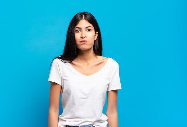 Jeune jolie femme hispanique avec une expression maladroite, folle et surprise, des joues gonflées, se sentant bourrée, grosse et pleine de nourriture