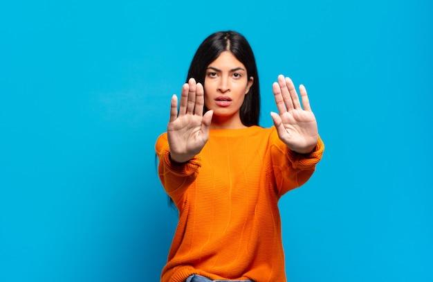 Jeune jolie femme hispanique à la grave, malheureuse, en colère et mécontente d'interdire l'entrée ou de dire arrêter avec les deux paumes ouvertes