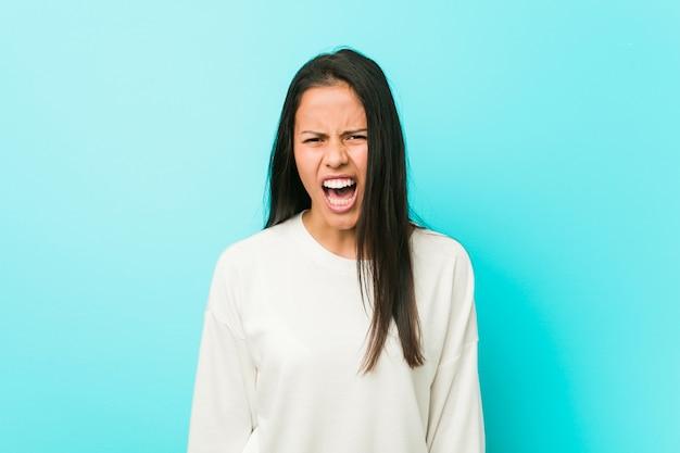 Jeune jolie femme hispanique hurlant de colère et d'agressivité.