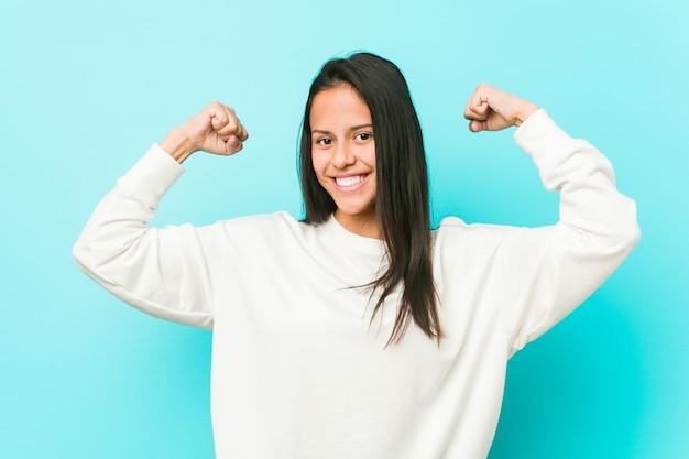 Jeune jolie femme hispanique montrant le geste de la force avec les bras, symbole du pouvoir féminin