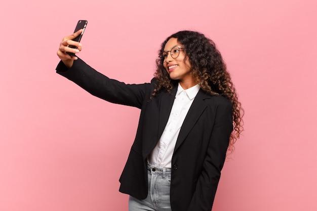 Jeune jolie femme hispanique prenant selfie